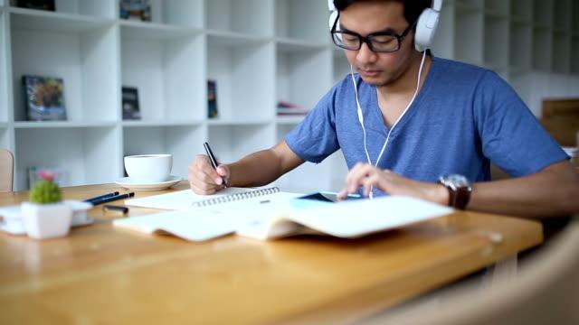 asiatiska man skriva och lyssna på musik innan du dricker kaffe - t tröja bildbanksvideor och videomaterial från bakom kulisserna