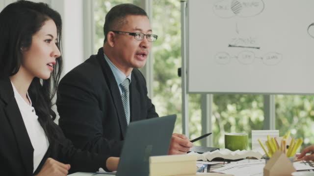 asiatiska manager och hans team hört deras arbete - officer militär grad bildbanksvideor och videomaterial från bakom kulisserna
