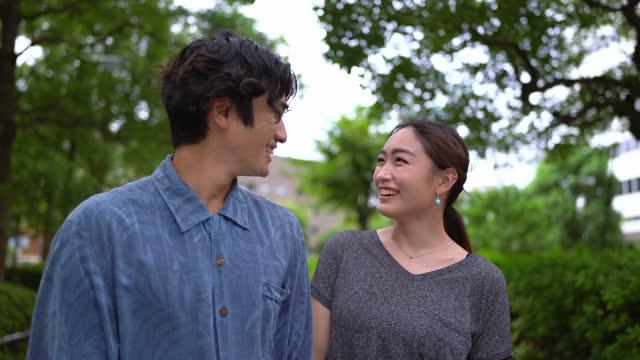外に立つアジアの夫婦、目を見て - 向かい合わせ点の映像素材/bロール