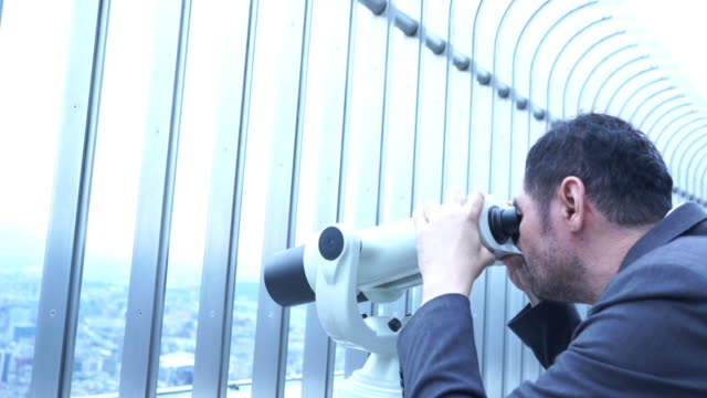 asian mature businessman using binocular look city view - looking through an object stock videos & royalty-free footage