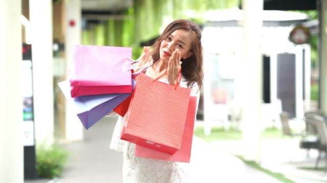 Asian mature businesswoman cheerful with shopping bags,blowing kiss ,slow motion