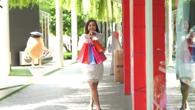 Asian mature businesswoman cheerful with shopping bags,slow motion