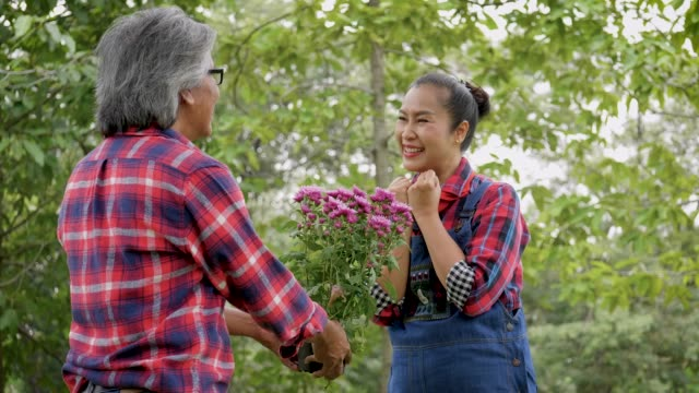 Asian mature man offering flowering plants to his wife, Mature couple relaxing and spending time together at park outdoors