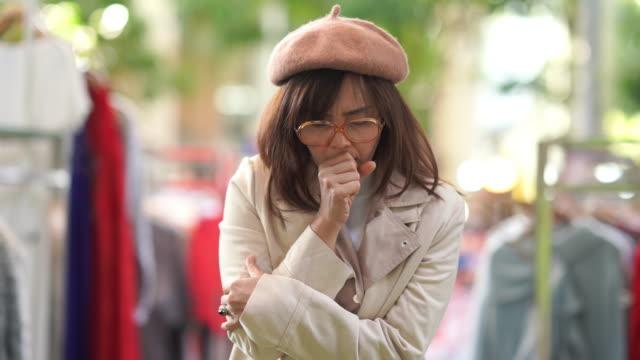 stockvideo's en b-roll-footage met aziatische volwassen vrouw winkelen jurk in de winkel, hoesten - chronische ziekte