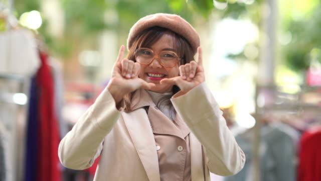vídeos de stock e filmes b-roll de asian mature woman shopping dress in retail store , shaka sign - aloha