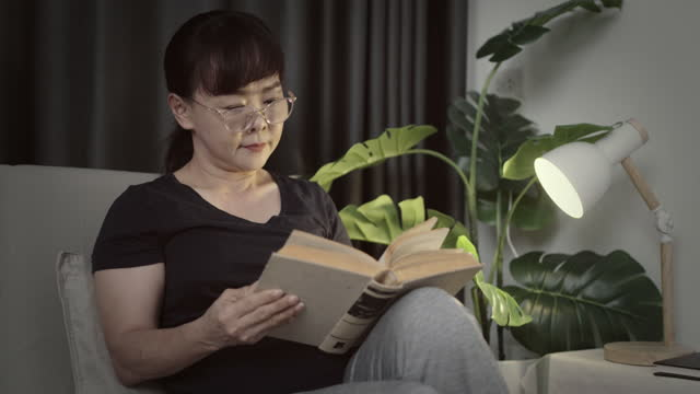 asian mature woman sitting on sofa and reading a book in her room. - 40 44 years stock videos & royalty-free footage