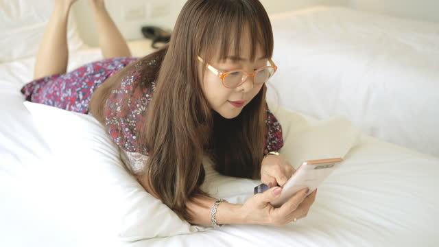 asiatische reife frau mit einem handy im schlafzimmer. - one mature woman only stock-videos und b-roll-filmmaterial