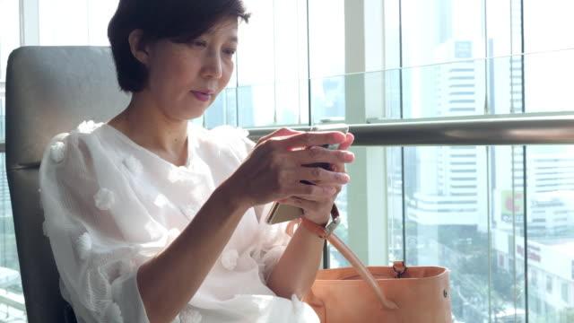 vídeos de stock, filmes e b-roll de mulheres maduras asiáticas que usam o telefone móvel - dispositivo de informação portátil