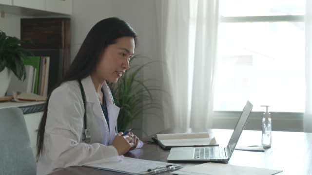 vídeos y material grabado en eventos de stock de profesional médico asiático haciendo una cita remota - visita a domicilio