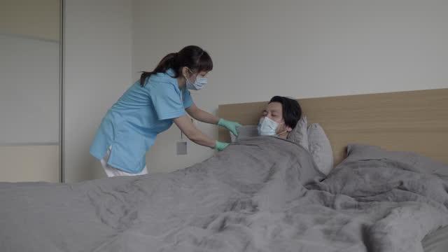 アジアの医療従事者は、自宅で彼のベッドに横たわっている病気の患者の世話をします - 保護用手袋点の映像素材/bロール