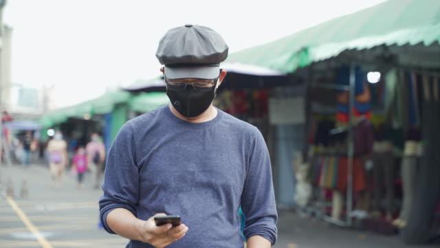 vídeos de stock, filmes e b-roll de homens asiáticos de 40 a 50 anos de uso casual, usando máscaras para proteger do coronavírus.  leitura de e-mails ou mensagens online em seus smartphones. - send