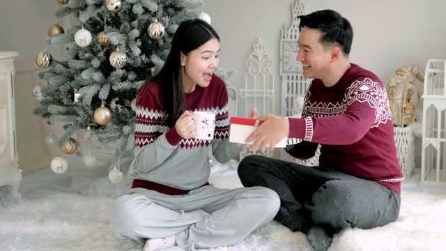 asian men and women lovers give gifts at christmas in the living room of his house. - jumper stock videos & royalty-free footage