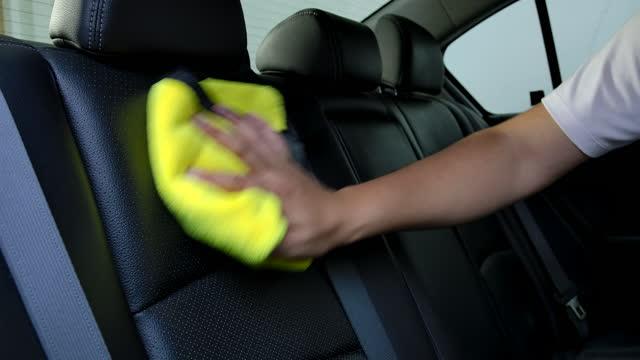 gli uomini asiatici stanno pulendo l'interno delle auto dei clienti presso il negozio di dettagli auto. - interno di automobile video stock e b–roll