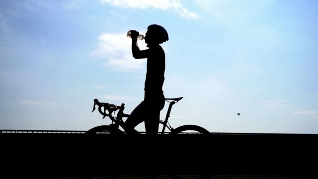 Asian men are cycling and drinking water.