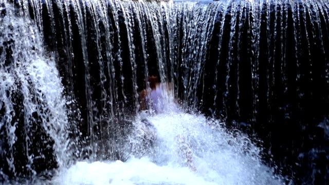 vídeos de stock e filmes b-roll de asian men are playing waterfall in national park - hd format