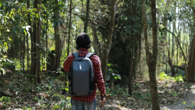 Asian men backpacks and traveler walking together and happy are taking photo on forest  ,Relax time on holiday concept travel
