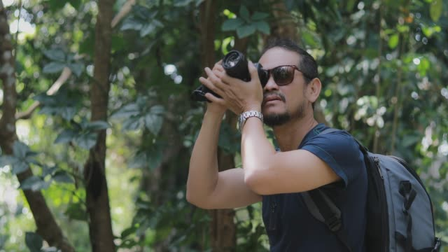 asian men backpacks and traveler walking together and happy are taking photo on forest  ,relax time on holiday concept travel - photographer stock videos and b-roll footage