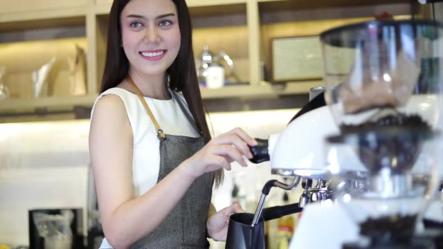 Asian men Barista using coffee machine in coffee shop counter - Working woman small business owner food and drink cafe concept
