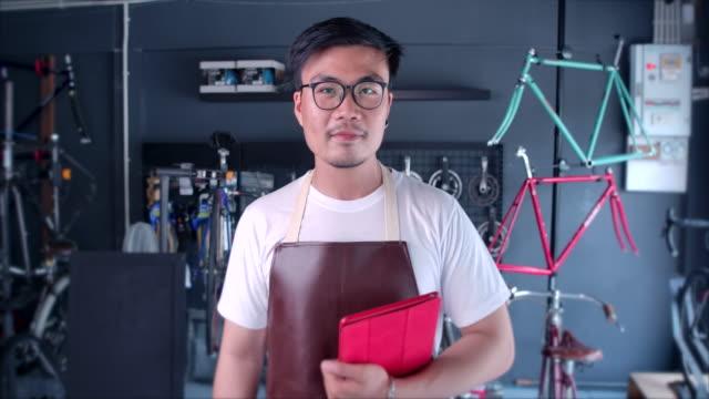 asian men bicycle shop besitzer kleinunternehmen stehen, um kunden im shop willkommen zu heißen - werkzeug stock-videos und b-roll-filmmaterial