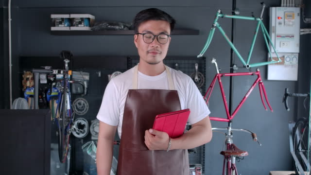 vídeos de stock e filmes b-roll de asian men bicycle shop owner small business standing to welcome customers inside the shop - full length