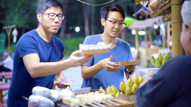 Asian Men buying street in Thai Traditional market