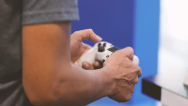 uomini asiatici amici competitivi che giocano ai videogiochi ed eccitati allegri felici a casa - remote control video stock e b–roll