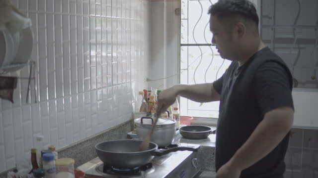 asian men cooking in the kitchen. - kitchen stock videos & royalty-free footage
