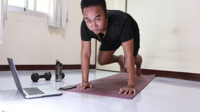 asian men exercising and working out at home, he is watching youtube videos and learning the exercises. - bodyweight training stock videos & royalty-free footage