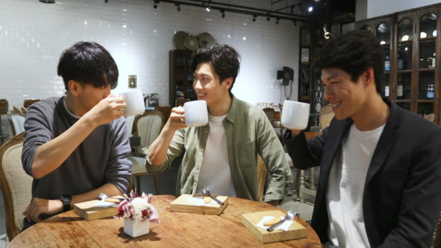asian men having a celebratory toast with coffee in a cafe - honour stock videos & royalty-free footage