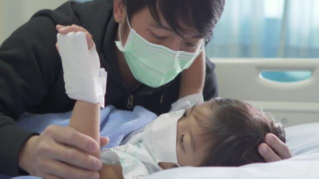 asiatiska män håller sin lilla son på sängen på sjukhus. - enbarnsfamilj bildbanksvideor och videomaterial från bakom kulisserna