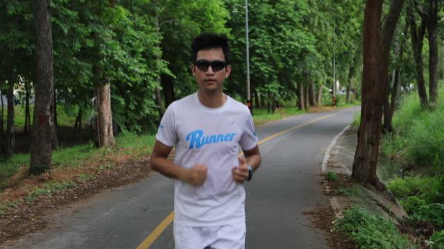 アジアの男性がジョギングをして公園で走る - sunglasses点の映像素材/bロール