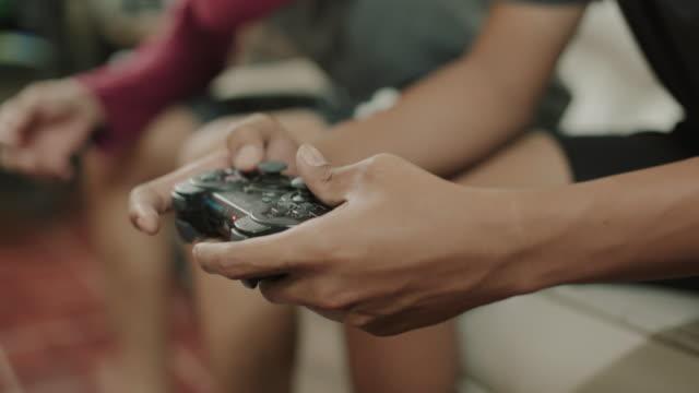 ビデオゲームをしているアジアの男性 - テレビのリモコン点の映像素材/bロール