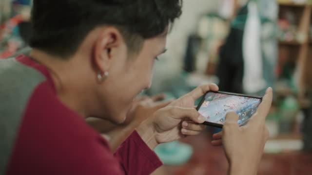 リビングルームで友人とビデオゲームをしているアジアの男性 - モバイルアプリ点の映像素材/bロール