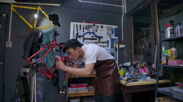 asian men wear glasses he is the owner of a bicycle shop. is a small business he is fixing the bike and spinning the wheel. he is using a tablet to check the product, see the professional. - bicycle stock videos & royalty-free footage
