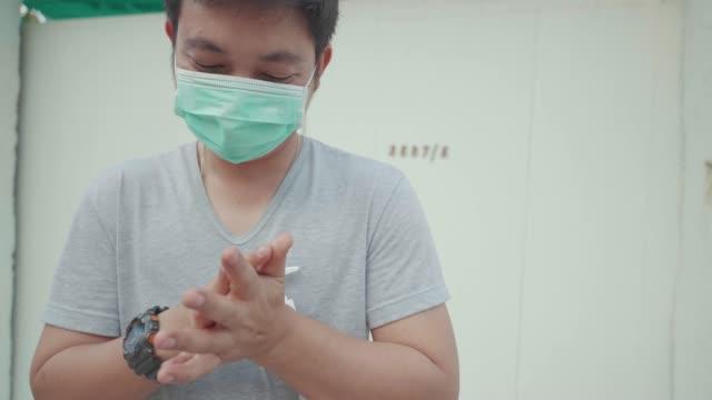 vídeos de stock e filmes b-roll de asian men wear mask face wash hands with gel, protect virus covid-19. - prevenção de doenças