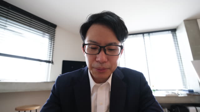 asian mid-adult businessman talking on web conference from home - webcam stock videos & royalty-free footage