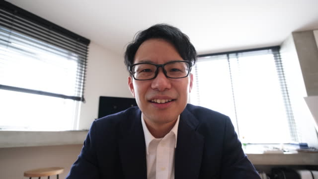 asian mid-adult businessman talking on web conference from home - asking stock videos & royalty-free footage