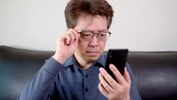 Asian middle-aged male trying to read something on his mobile phone. presbyopia, myopia.