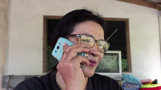 asian middle-aged woman using smart phone - only mature women stock videos & royalty-free footage
