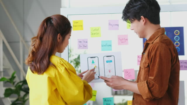 asian mobile application developers testing the code and fixing the issues, asia man and woman, ux,ui coworker, discuss for mobile app smartphone - solutions stock videos & royalty-free footage