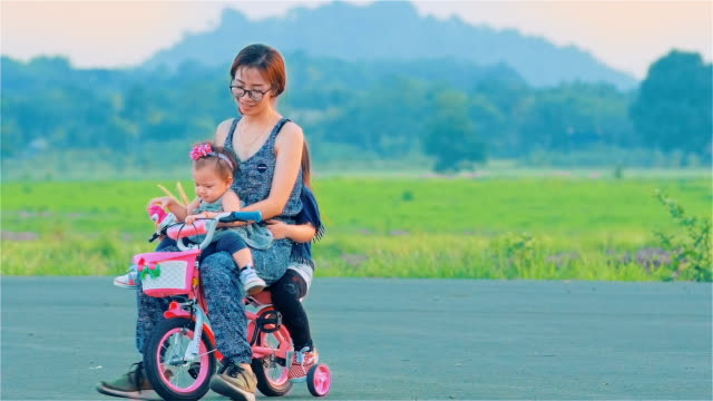 asian mom and daughter cycling together - baby girls stock videos & royalty-free footage