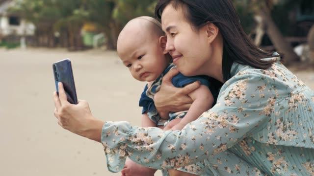 asiatiska mamma och hennes pojke (6-11 månader) tar en selfie - 6 11 månader bildbanksvideor och videomaterial från bakom kulisserna