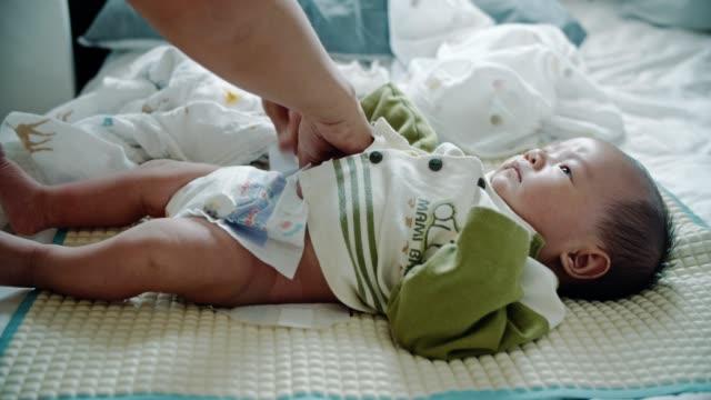 vídeos y material grabado en eventos de stock de asiática mamá cambiando pañal a su bebé niño(0-1 meses) - bebés 0 1