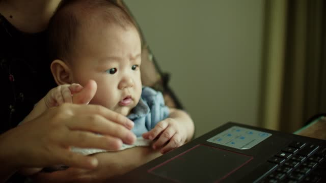 asian mom working on laptop with her son at home - using laptop stock videos & royalty-free footage