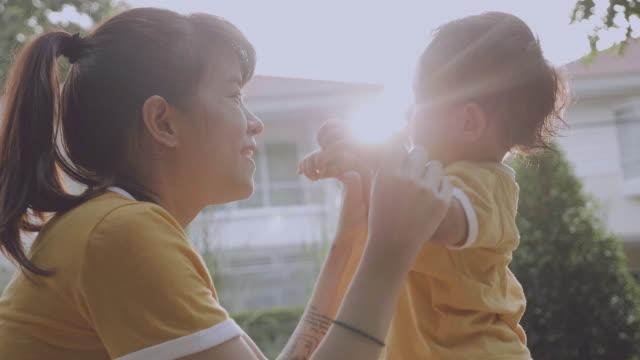 vídeos de stock, filmes e b-roll de asiático mãe e bebê (6-11 meses) menino no parque - solar flare