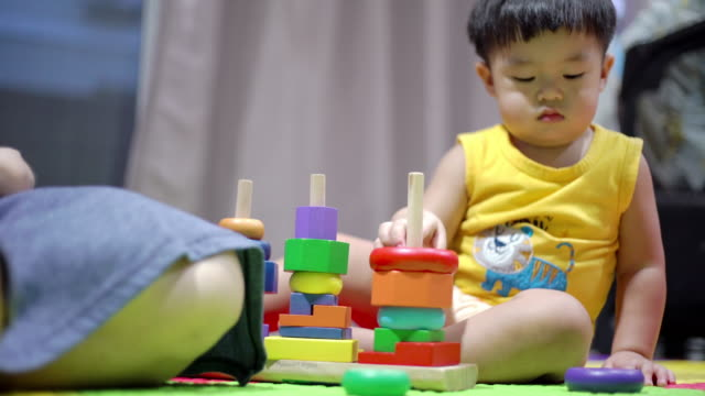 asian mother and baby boy playing wood block together on the mat in the living room at home - baby boys stock videos & royalty-free footage