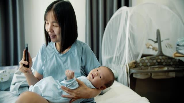 vidéos et rushes de mère asiatique et bébé (2-5 mois) boy video chatter sur mobile phone - 2 5 mois