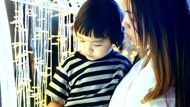 Asian mother and baby girl with travel at new year event -new year light decoration event