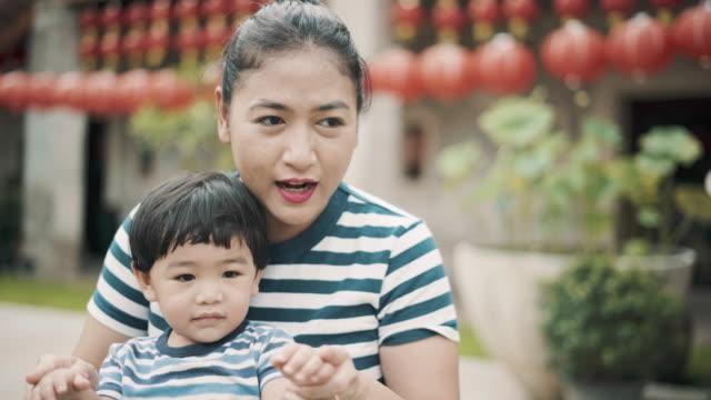 Asiatisk mor och barn ha roligt utomhus.