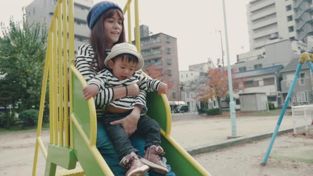 アジアの母と赤ちゃん秋の公園で遊ぶ